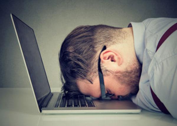 Мужчина в очках положил голову на клавиатуру ноутбука