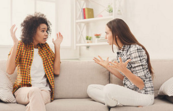 Две девушки беседуют на диване. Одна агрессивно настроена