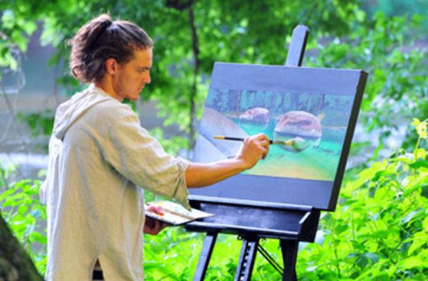 Парень рисует картину на природе