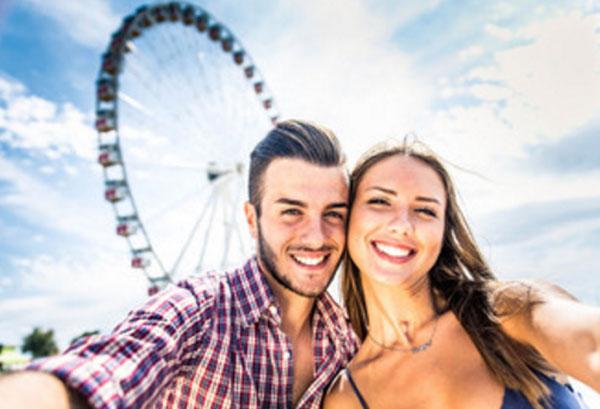 Счастливая пара на фоне чертового колеса