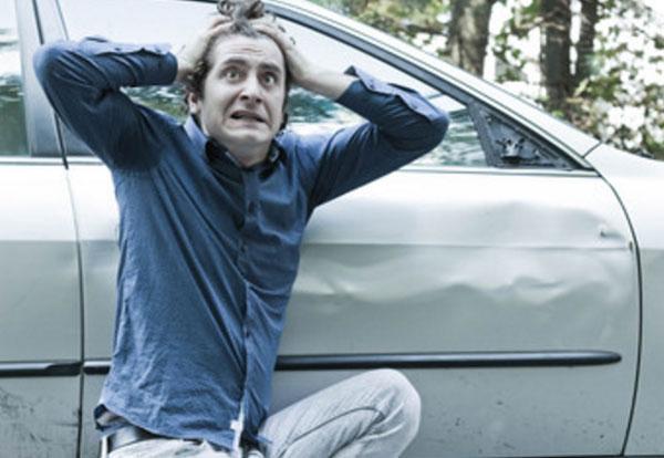Мужчина в шоке, держится за голову. Сидит рядом со своей машиной, у которой разбито крыло
