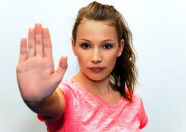 Девушка знаком руки показывает свой отказ