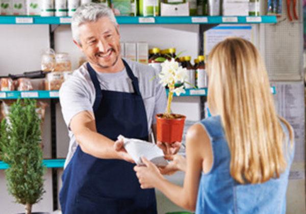 Женщина с продавцом. Она покупает цветок в горшке