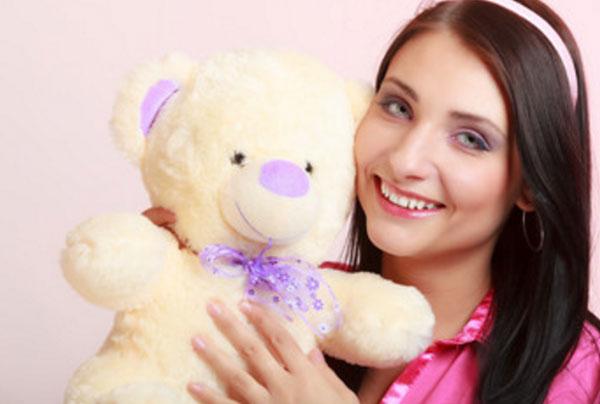 Девушка с обручем на голове и плюшевым медведем в руках