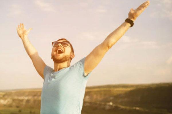 Мужчина радуется, подняв руки к небу
