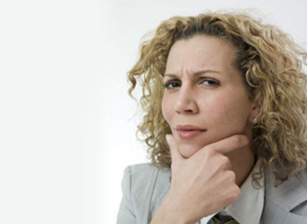 Женщина в задумчивости, смотрит с недоверием