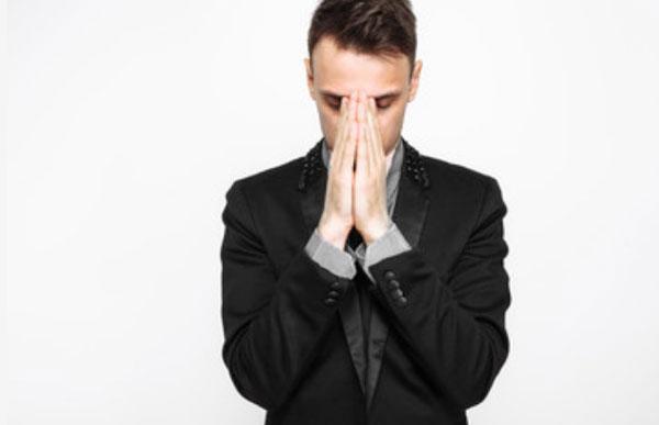 Мужчина стоит и прикрывает свое лицо сложенными ладонями