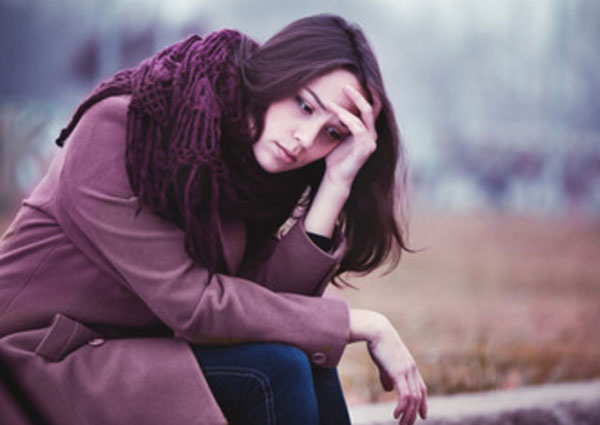Одинокая расстроенная девушка сидит на скамейке