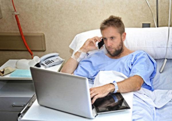 Мужчина продлжает работать на ноутбуке, лежа в палате