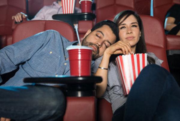 Расстроенная девушка ест попкорн, а парень уснул на ее плече