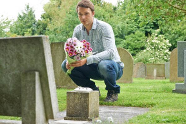 Мужчина сидит возле могилы с цветами в руках