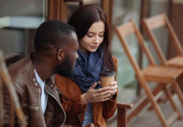 Девушка европеоидной расы пьет кофе рядом с парнем негроидной расы