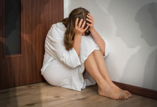 Женщина сидит на полу и держится за голову, пряча лицо. Вокруг нее тени людей