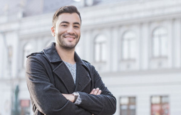 Счастливый парень стоит на улице и улыбается