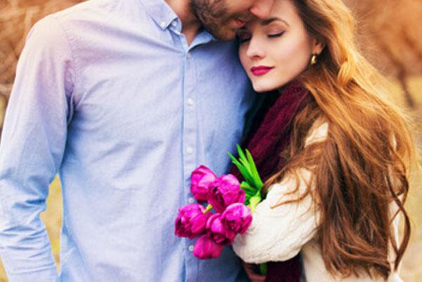 Парень обнимает девушку. Она к нему прижимается. В руке у девушки букет цветов