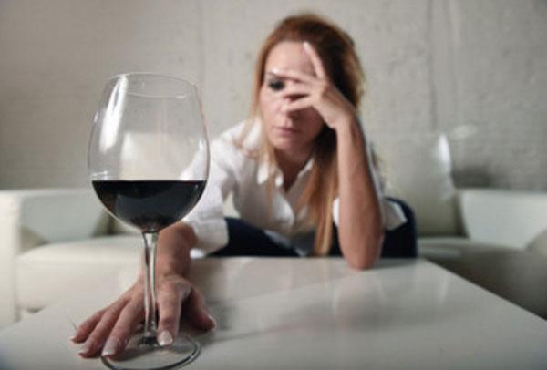 Плохо выглядящая женщина тянется за бокалом вина
