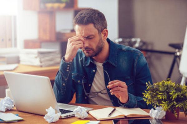 Отчаявшийся мужчина сидит перед ноутбуком