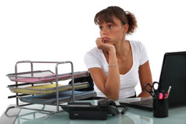 Печальная, расстроенная женщина сидит на рабочем месте и не знает, что делать