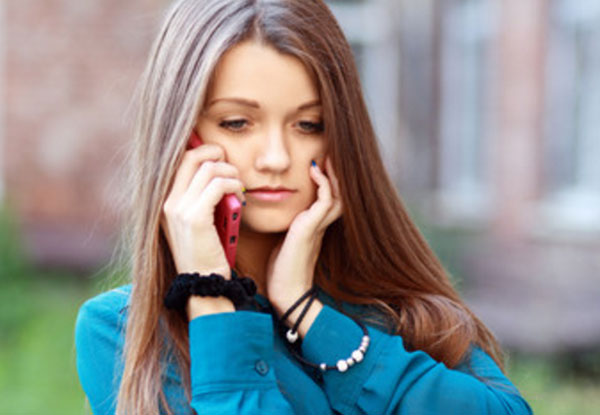 Девушка расстроенная, держит возле уха телефон