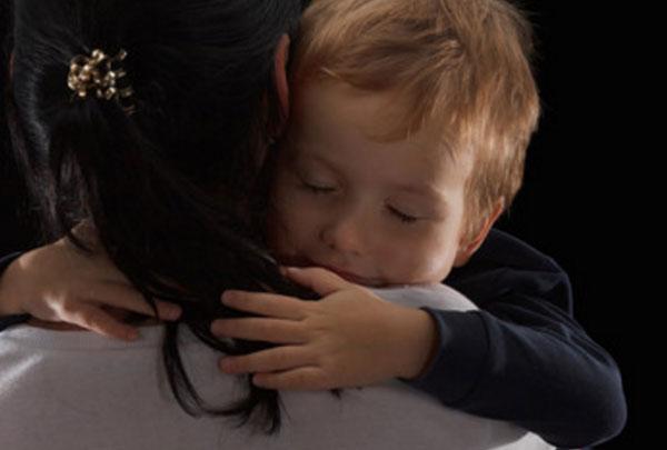 Мальчик крепко обнимает женщину, которая держит его на руках