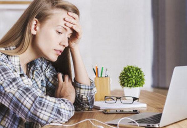 Девушка в расстроенных чувствах читает сообщение. У нее открыт ноутбук