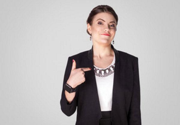 Самодовольная женщина стоит, указывая пальцем на себя