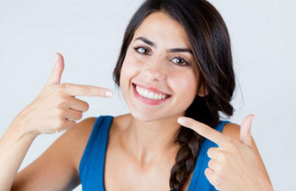 Девушка улыбается и показывает пальцами на свою улыбку