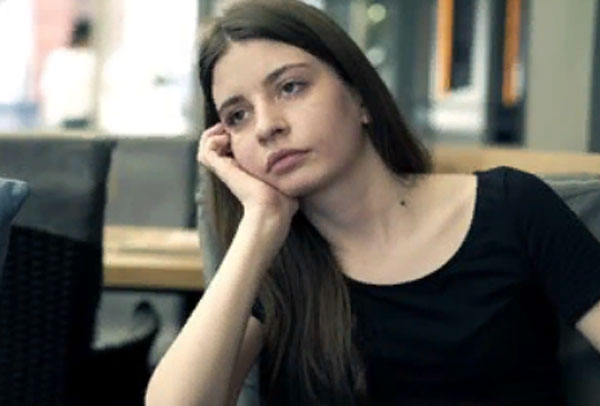 Скучающая девушка сидит в офисе