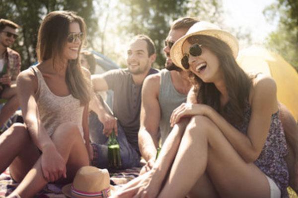 Компания молодых девушек и мужчин на пикнике