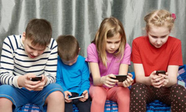 Четыре ребенка сидят и смотрят в свои телефоны