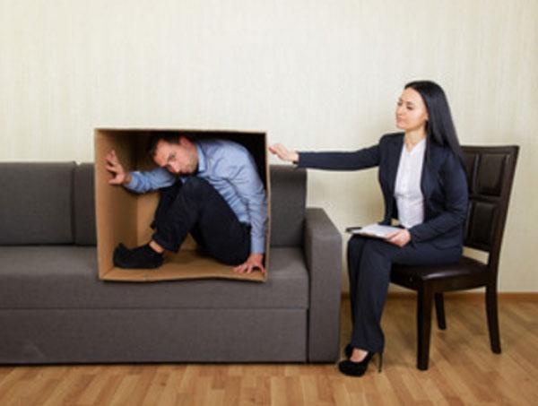 Мужчина сидит в коробке, которая стоит на диване. Рядом на стуле сидит психолог