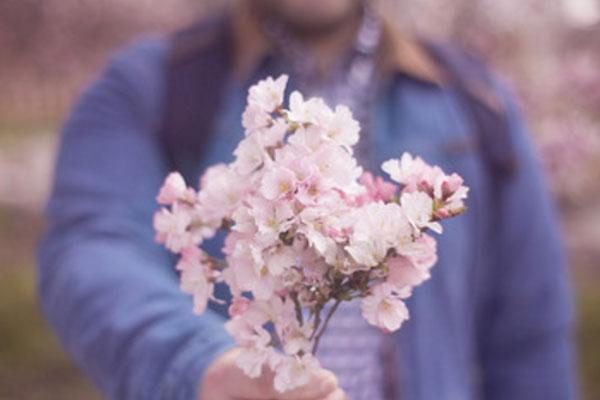 Парень держит маленький букет розовых цветочков
