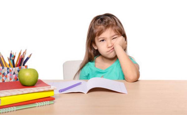 Девочка подпирает голову рукой. Она недовольна. На столе лежат уроки