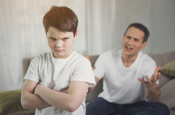 Сердитый мальчик на переднем плане. На заднем орущий отец