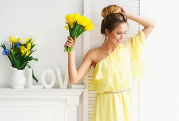 Девушка в светло-желтом платье с букетом желтых тюльпанов в руке