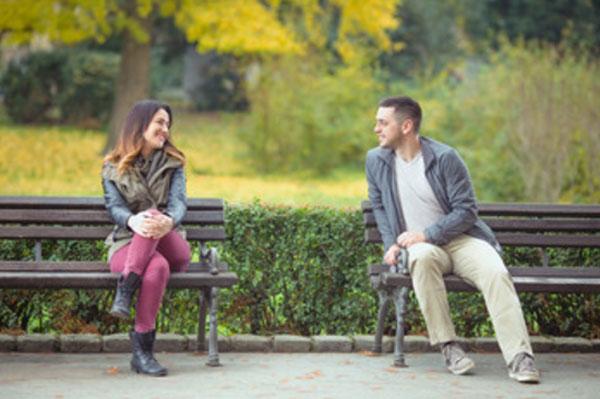 Парень и девушка сидят на разных скамейках. Смотрят друг на друга влюбленным взглядом