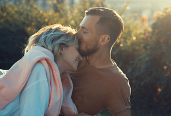 Счастливая пара. Мужчина целует девушку в лоб