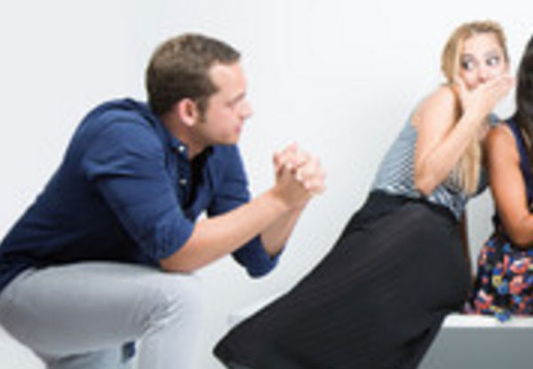 Парень стоит на колене и о чем-то просит у девушки. Она уклоняется от него, прикрывает рот