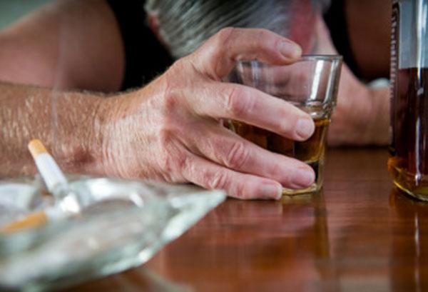 Мужчина опустил голову на стол. В руке у него рюмка с алкоголем. На столе лежат окурки