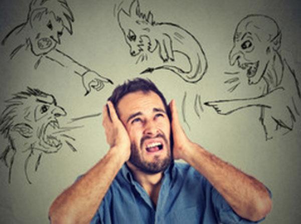 Мужчина в ужасе, держится за голову. На стене нарисована разная нечисть, которая ему что-то говорит