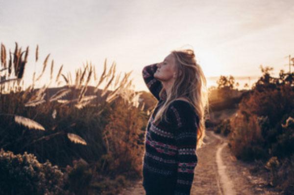 Женщина стоит возле тропинки, наслаждается природой