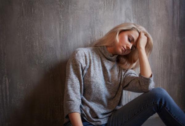 Замученная женщина сидит на полу