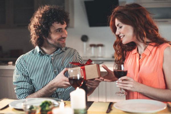Мужчина преподносит женщине подарок за романтическим ужином