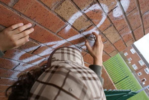 Подросток расписывает стену