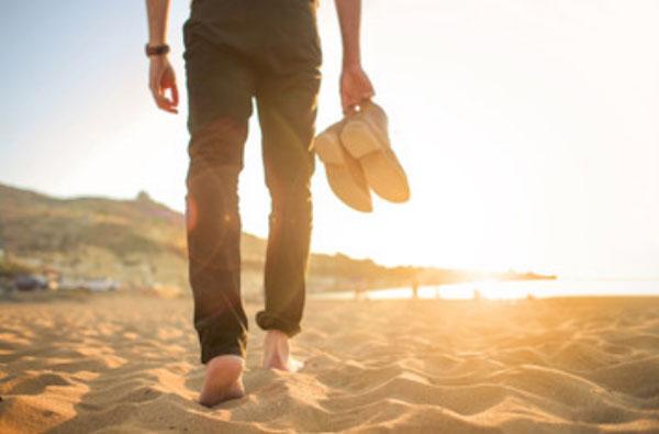 Мужчина идет босиком по песку