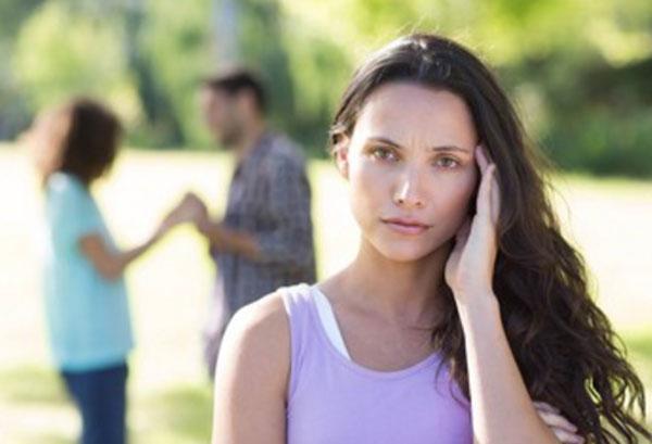 Женщина держится за голову. На задем плане мужчина беседует с женщиной, взявшись за руки