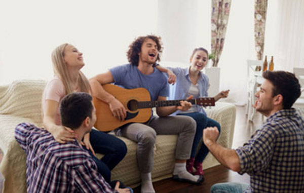 Компания друзей. Душа компании играет на гитаре и поет песню. Все на него смотрят