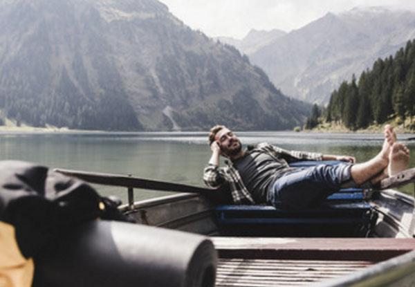 Счастливый мужчина лежит в лодке