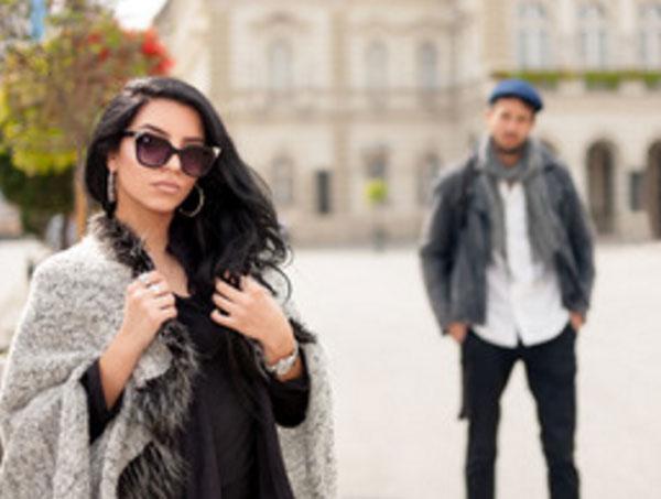 Девушка в пальто, в солнцезащитных очках. Сзади парень