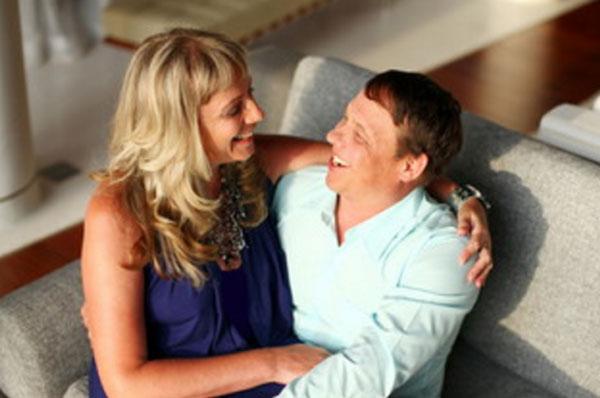 Жена сидит на коленях мужа, они счастливы, мило общаются